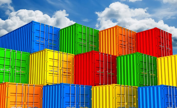 Colorful stacked freight shipping containers against clouds